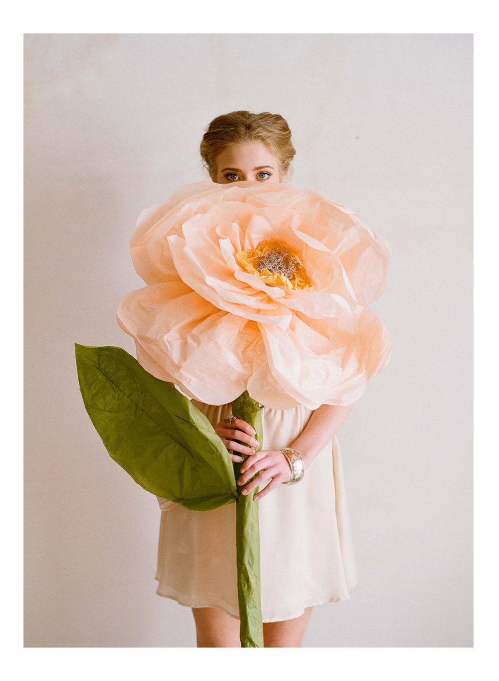 woman holding giant peach paper flower with green stem