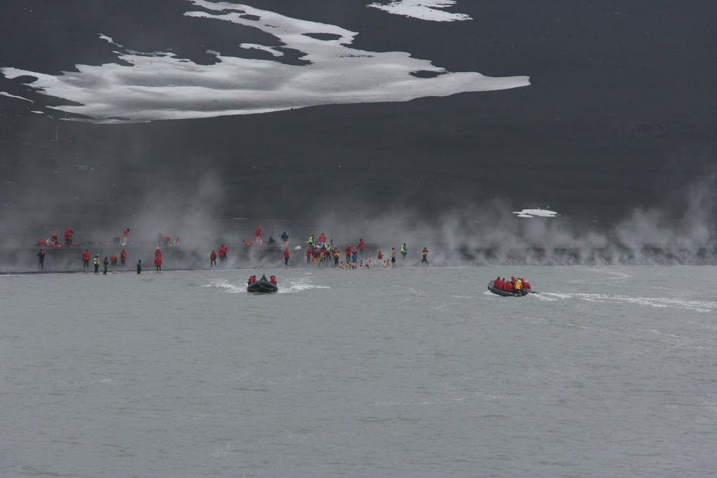 long shot of hot springs on Deception Island. Steam rises from the water, snow can be seen in the background
