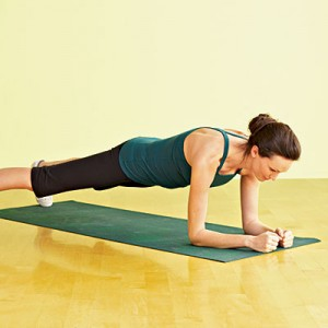 Woman resting on arms and toes in plank position
