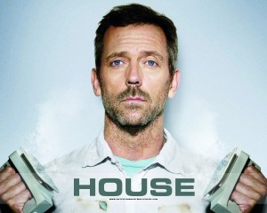 Dr House is holding a defibrilator in his hands.