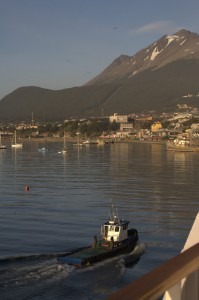 Photo taken from a ship of the water and coastline of Ushuaia, Argentina. A small boat is visible in the foreground; mountains and homes in the background