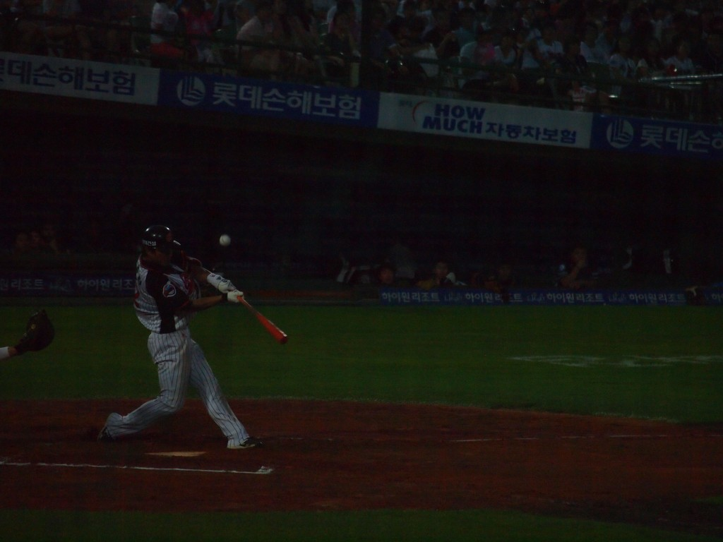 A man playing baseball swings at the ball and misses.