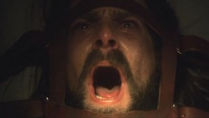 Baltar's face, his head restrained with leather straps. He's screaming.