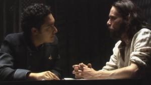 Gaeta and Baltar sit calmly at a table.