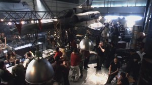 A homemade bar on Galactica - there's a fighter plane hanging, everything looks  like it was made from leftover or stolen bits of machinery - mechanical and homemade, it's full of people.