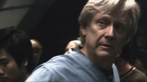 Doctor Roberts - a white man in his fifties, with floppy white hair, wearing scrubs.