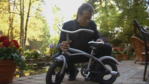 Adama, in a house we've never seen before, inspects a small bicycle.
