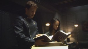 Dee and Lee in their quarters, looking at thick leather-bound books.
