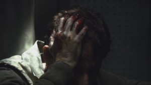 Cabot, dirty, holds his head in his hands, his fingers bloody.