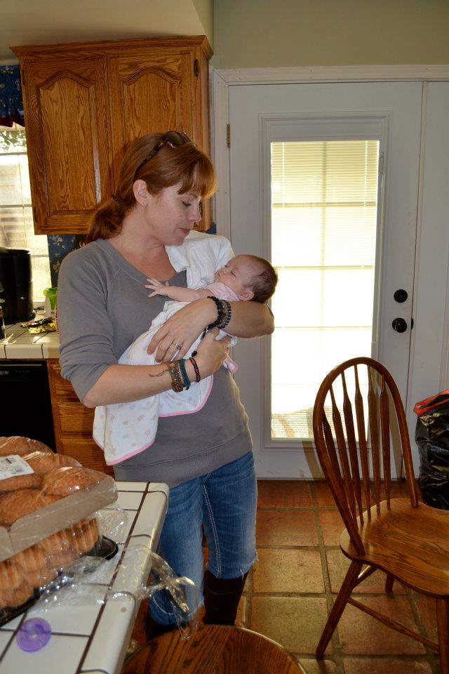 Photo of Kym in a kitchen holding baby niece and bouncing her to sleep