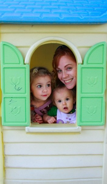 photo of Kym and two nieces poking heads out of the window of a cream playhouse with green shutters and a blue roof
