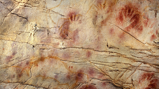 cave painting where red pigment has been sprayed to show the outline of hands