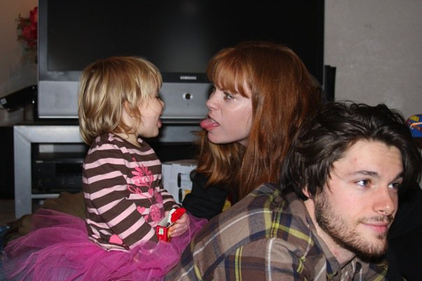photo of Kym, Charlie and Steven, Kym sticking her tongue out at Charlie, who is sitting on Steven's back