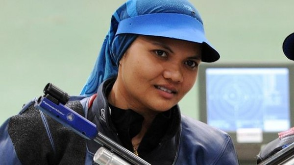 Close-up of Nur with rifle, in shooting gear with cap and scarf