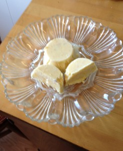 On a fancy glass plate, two mounds of yellow-ish mango kulfi are set. One has been cut in half.