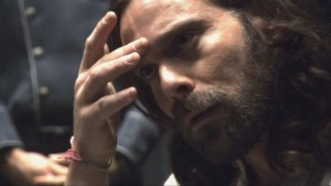 Closeup on Baltar, with his hand on his face.