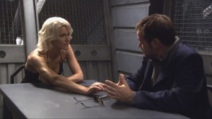 Caprica Six and Lampkin sit at a table, arms stretched towards each other.