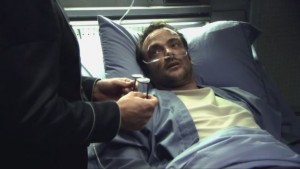 Lampkin, lying in sick bay, confessing to taking people's things. Lee's in the foreground, holding Roslin's glasses.