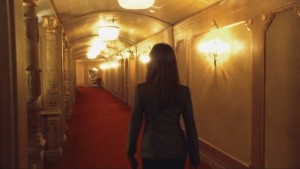 Roslin, walking away from the camera, down an ornate hallway.