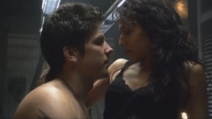 Shirtless Anders and scantily-clad Tory are shown in profile, about to kiss