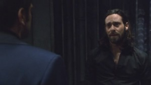 Baltar, in a black buttoned shirt, in his cell, looking confused.