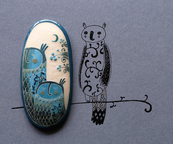 close-up of blue-white brooch featuring owls, branches, and the moon