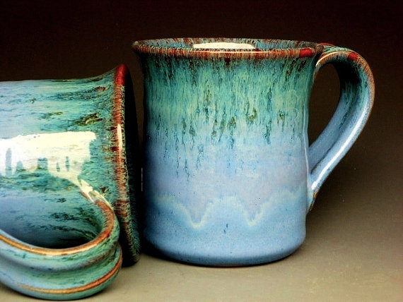 close-up of two blue-green ceramic coffee mugs
