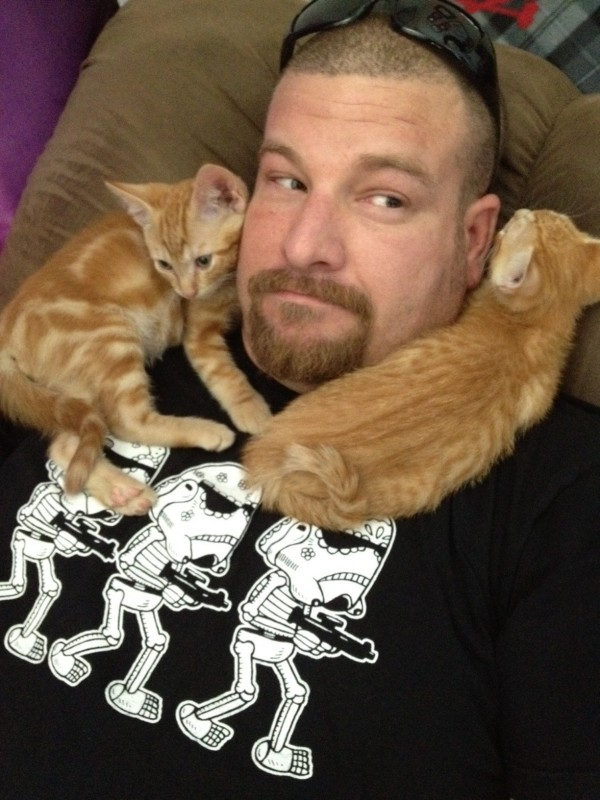 photo of Jon with an orange tabby and tiger kitten wrapped around his neck wearing an awesome Storm Trooper Dio De Los Muertos shirt