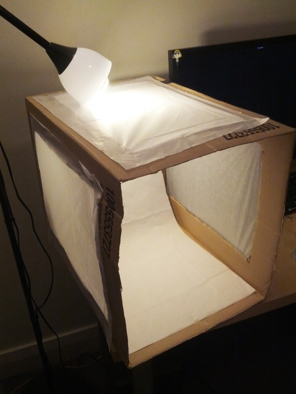 Tissue paper covers the holes on the box and a lamp is positioned over the top.