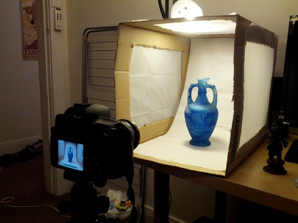 A blue vase is inside the lightbox and a camera is set up on a tripod, pointing at the vase. You can see the vase on the camera's screen.
