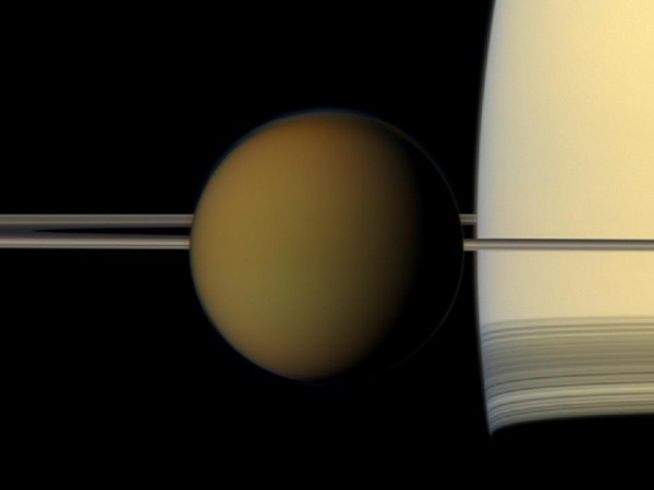 True-color photograph of Titan crossing in front of Saturn, with an edge-view of the rings.