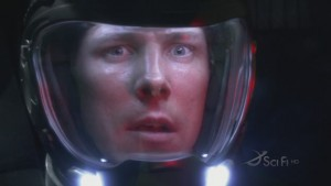 Sam Anders, in a helmet, looking scared, with red light reflecting off his helmet.