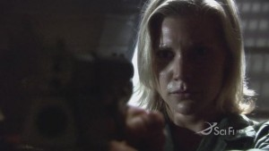 Starbuck, holding a gun, pointed at the camera.