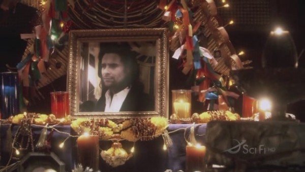 A shrine to Baltar - his photo is framed, surrounded by candles and lights.