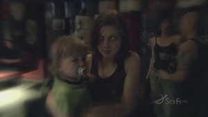 Cally and Nicky entering Joe's Bar. They are in focus, everything else is blurry and warped. Cally looks scared.