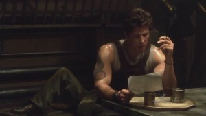 Sam Anders, sweaty, sitting at a table, smoking and reading a letter.