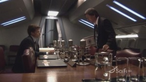 Lee and Zarek face each other on opposite sides of a long table. Lee is sitting, Zarek looks down at him.
