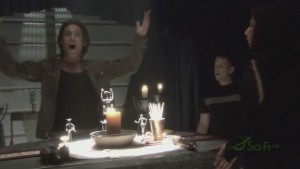 Baltar stands behind an altar to the Gods of Kobol. He is yelling, his arms raised.