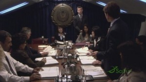 A long table, with people sitting on either side - the Quorum meeting. Lee is standing halfway along the table, Roslin is at the head.