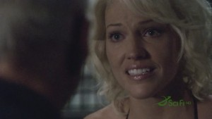 Caprica Six's face in closeup, and the back of Tigh's head