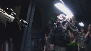 Head Six holds Baltar up by the armpits, forcing him to face a Marine.