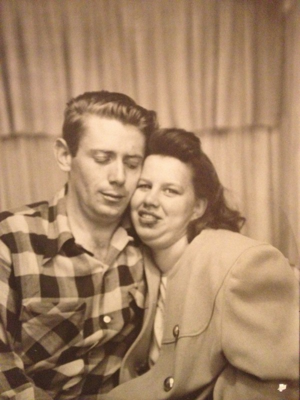 sepia colored photo booth picture of a young man in a plaid shirt and a young woman in a coat