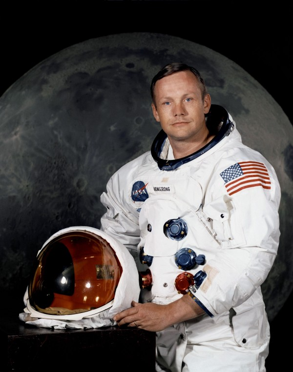 Official NASA portrait of Neil Armstrong in his space suit, with a photo of the moon as a backdrop