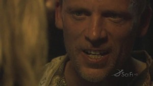 Leoben, his teeth are bared. The back of Starbuck's head is on the left side of the screen.