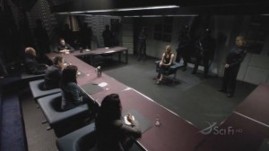 Tory, Roslin, Adama and Tigh sit at a table, Natalie sits in the middle of the room across from them, and Kara is up against a wall.  It looks like a tribunal or a court.