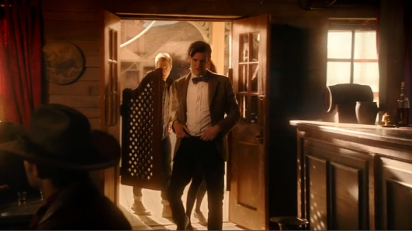 The Doctor, with Amy and Rory behind him, walk into an Old West-style bar.
