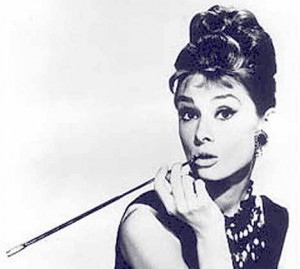 Audrey Hepburn with a long cigarette holder held to her lips