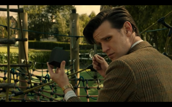 The Doctor, crouched down examining a small black cube with a small magnifying glass