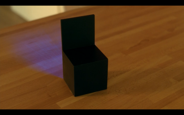 Black cube on a wooden table. One side has slid straight up, and blue light is coming from inside.