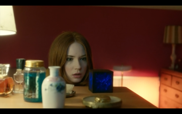 Amy looks at a cube on her dresser. The cube is lit from within with blue light.
